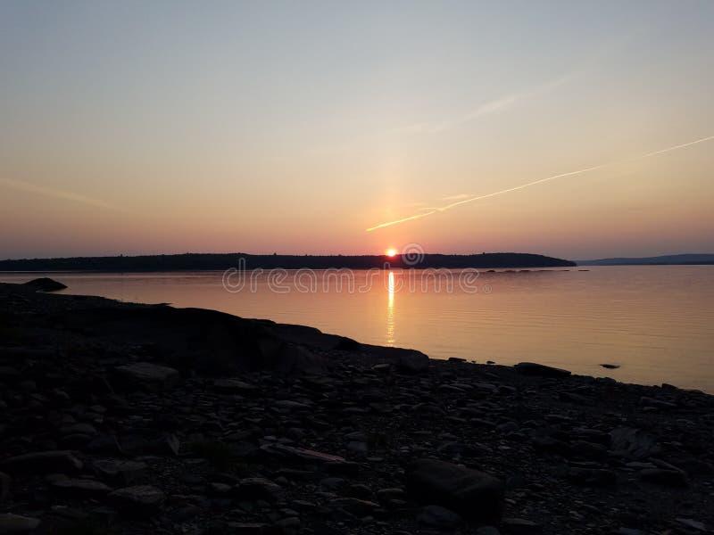 Solnedgånglandskap över en sjö fotografering för bildbyråer
