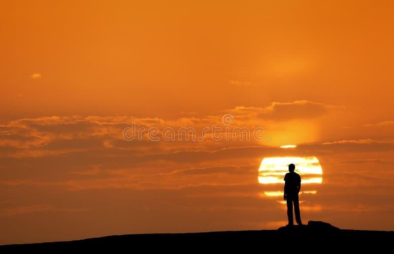 Solnedgånglandskap med konturn av en man med lyftta-upp armar royaltyfri foto