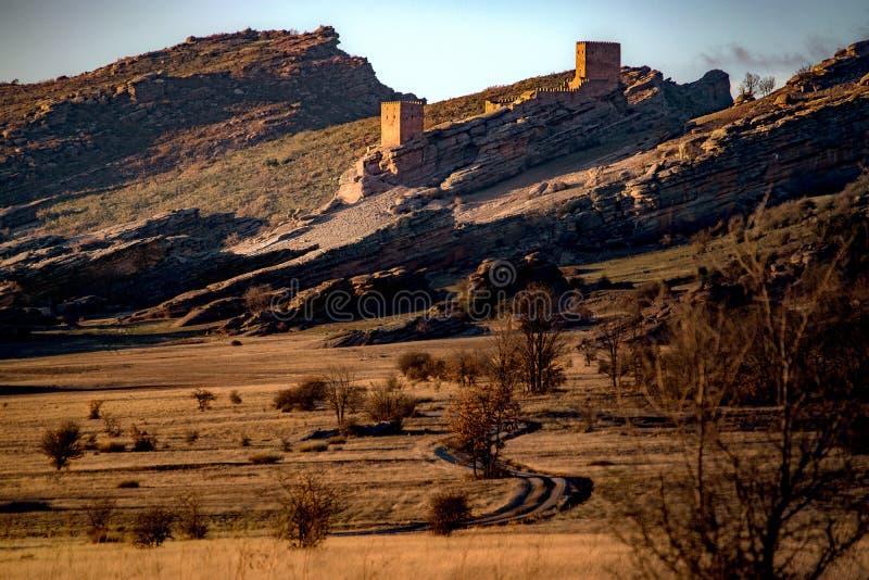 Solnedgånglandskap med några berg och en slottnolla arkivbild