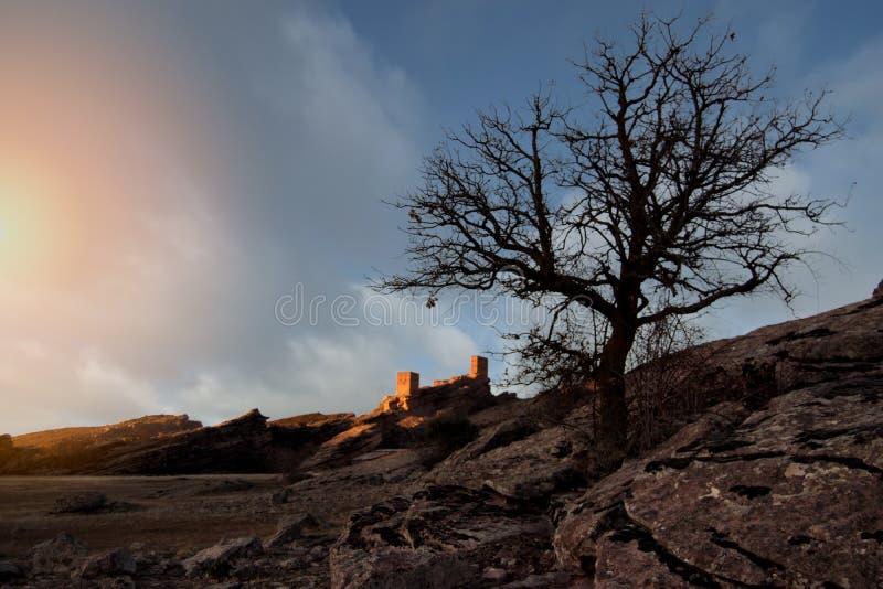 Solnedgånglandskap med några berg och en slottnolla arkivbilder
