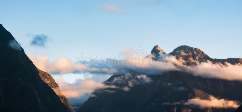 Solnedgångmoln och de rena klipporna på Milford Sound i Nya Zeeland royaltyfri foto