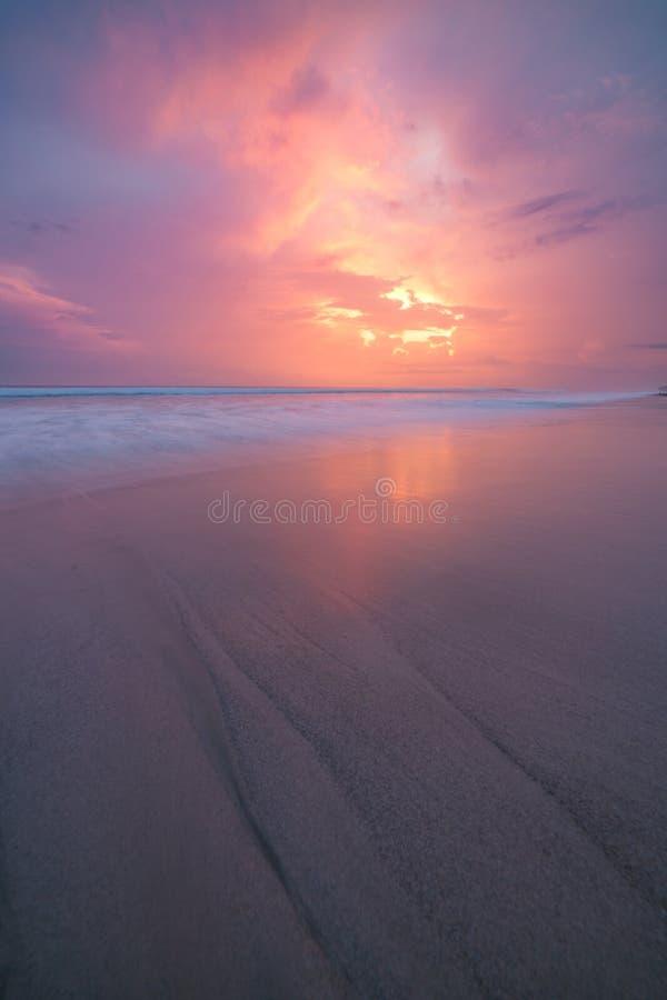 Solnedgångmoln och vågor på den tomma stranden arkivfoto