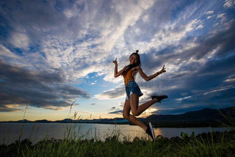 Solnedgångmolnstråle till den unga vuxna asiatiska womaen fotografering för bildbyråer