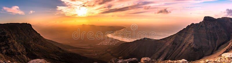 Solnedgångpanorama över för Famara Lanzarote för havsemesterortstrand öar kanariefågel, Spanien royaltyfri fotografi