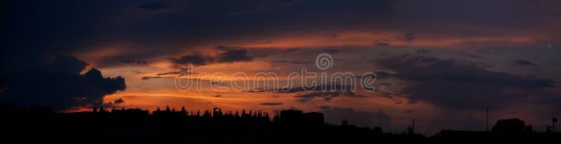 Solnedgångpanorama över staden med röda skuggor och moln royaltyfria foton