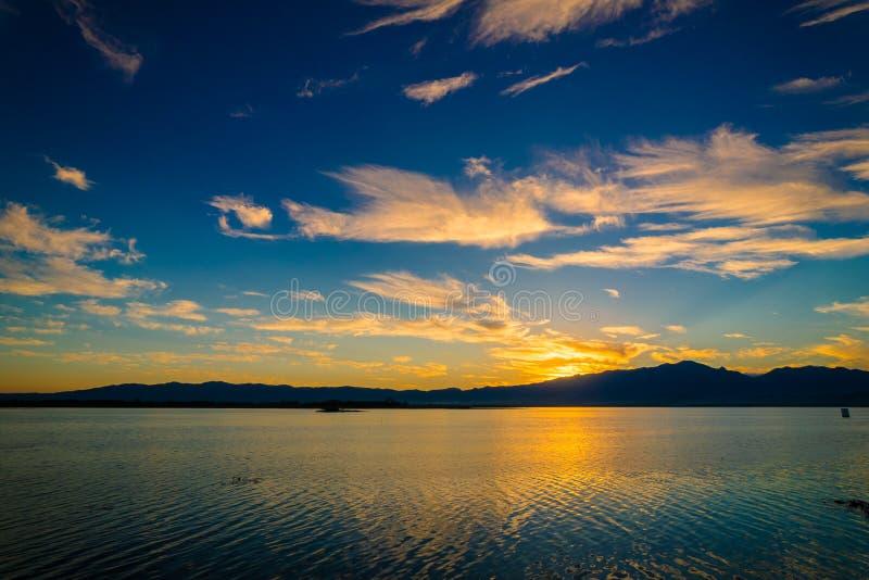 Solnedgångplatsskymning på sjön med blå himmel och clounds royaltyfri bild