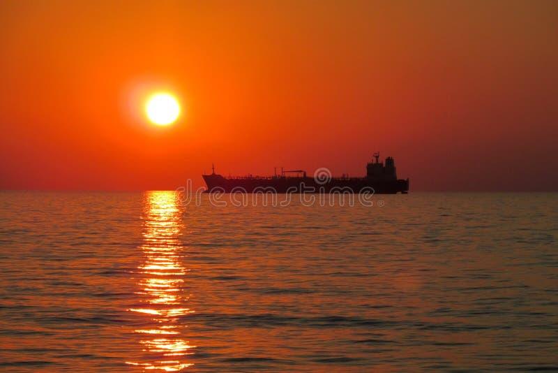 Solnedgångrött ljus ovanför havet, skeppkontur arkivbild