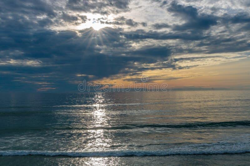 Solnedgångseascape, apelsinen, blått, gul himmel, med det marin- gröna havet för aqua, vit vinkar rullning in, Stilla havet, bakg royaltyfri foto