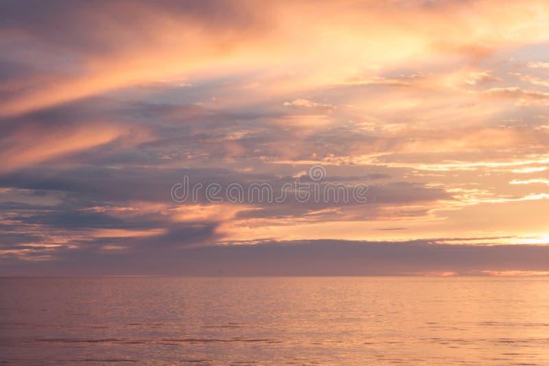 Solnedgångseascape, apelsinen, blått, guling, magentafärgad guld- himmel reflekterade i havsStilla havet, bakgrundsfotoet av sole arkivbilder