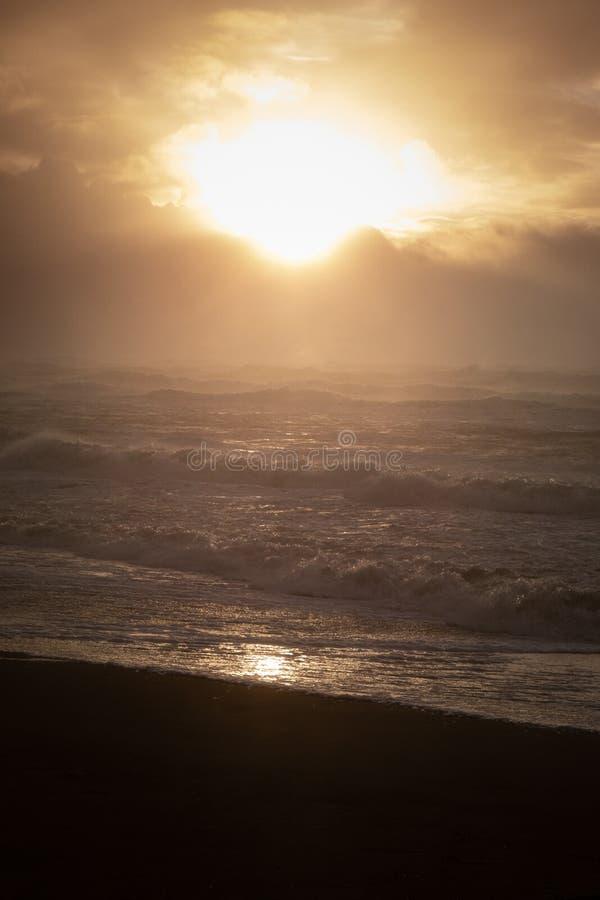 SolnedgångSeascape i brunt och svartar arkivfoto