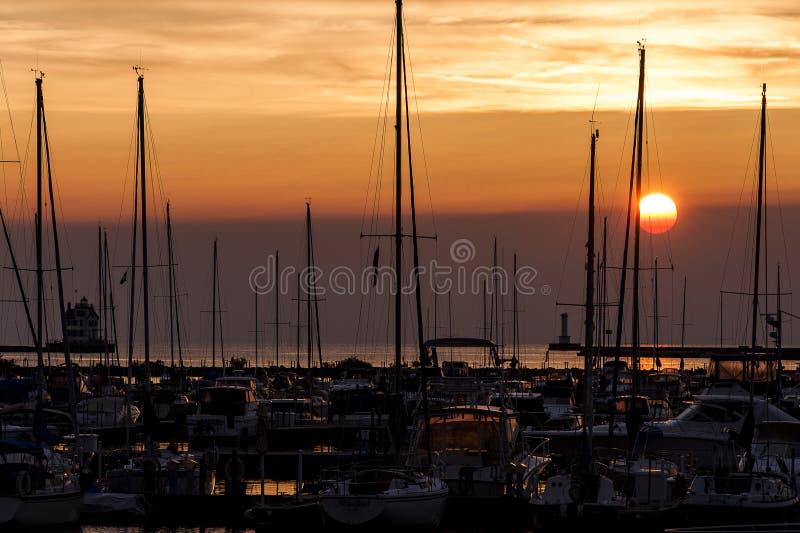 Solnedgångsikt av den Lorain hamnfyren & fartyget längs Lake Erie - Lorain, Ohio arkivbild