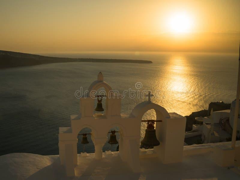 Solnedgångsikt av kyrkliga klockor på oia, santorini arkivbilder