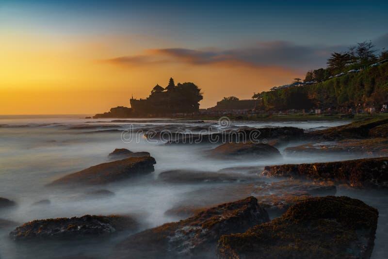 Solnedgångsikt av tanahlotttemplet på havet i den Bali ön en av mest berömd turist- dragning i Indonesien royaltyfria foton