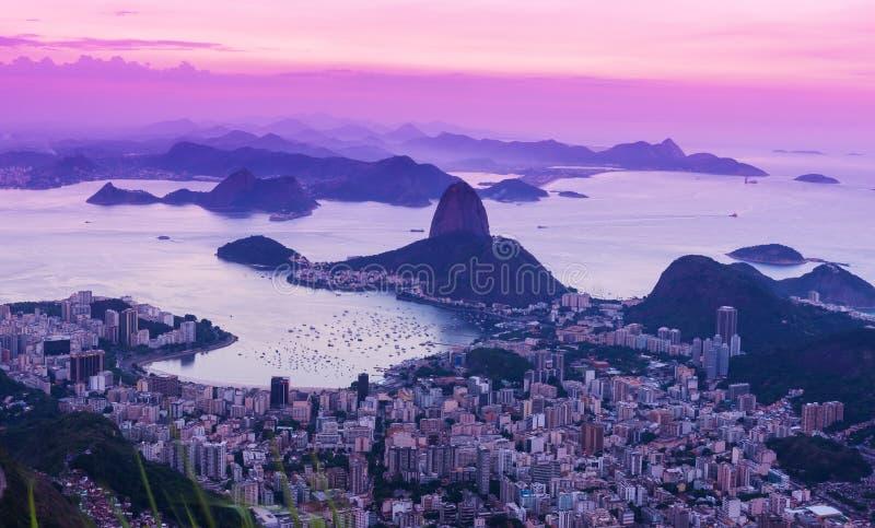 Solnedgångsikten av berget Sugar Loaf och Guanabara skäller i Rio de Janeiro royaltyfria bilder