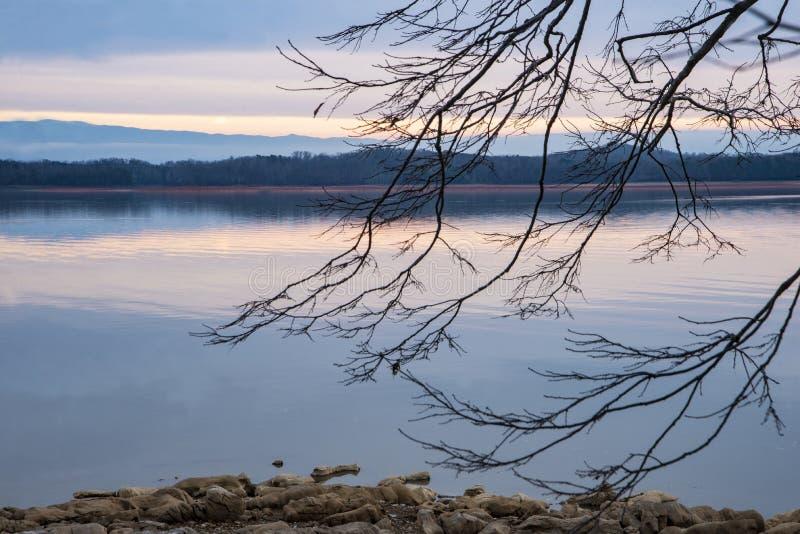 Solnedgångtimmar på en lokal sjö, i att blekna ljus royaltyfri foto