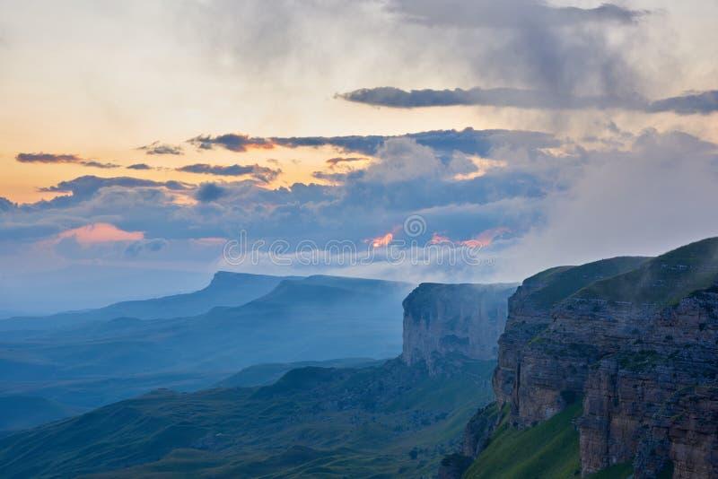 Solnedg?ng i bergen Solen skiner till och med dimman över bergskedjan Karachay-Cherkessia norr Kaukasus Ryssland arkivbild