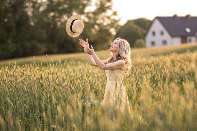 Solnedg?ng i sommar lantlig livstid En ung kvinna i f?ltet kastar en hatt arkivbilder
