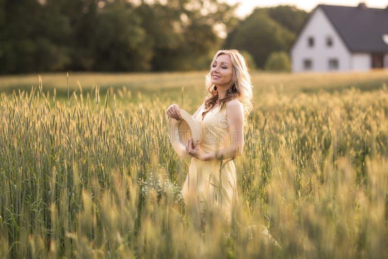 Solnedg?ng i sommar lantlig livstid En ung kvinna i f?ltet kastar en hatt royaltyfria bilder