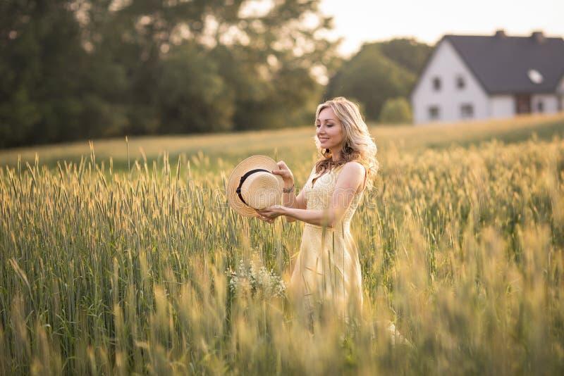 Solnedg?ng i sommar lantlig livstid En ung kvinna i f?ltet kastar en hatt arkivbild