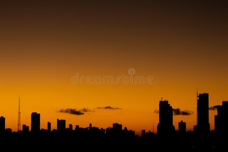 Solnedg?ng i staden, n?r den orange himlen kontrasterar med byggnaderna av raka linjer royaltyfri foto
