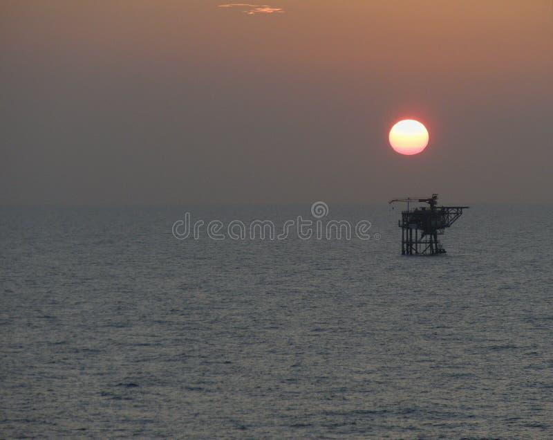 Solnedg?ng p? oljeplattformplattformen, Natuna hav Indonesien royaltyfri fotografi