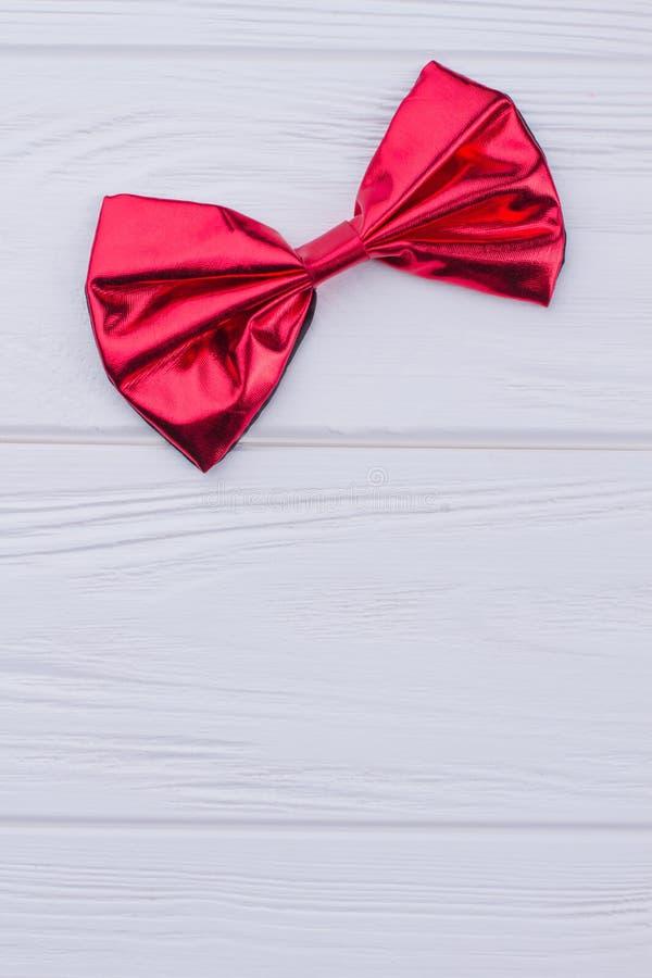 Solo arco rojo brillante en la madera blanca fotografía de archivo libre de regalías