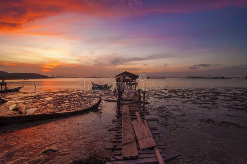 Solo barco y Boatshed de la salida del sol con el cielo ardiente imagenes de archivo