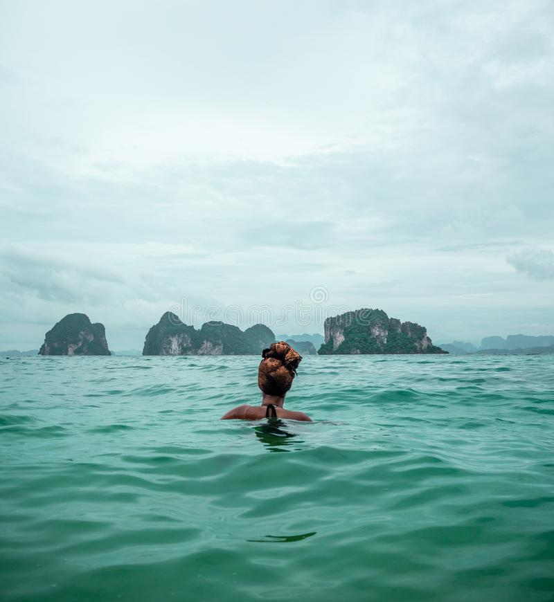 Solo Female Traveler Swimming in Phang Nga Bay, Thailand royalty free stock images