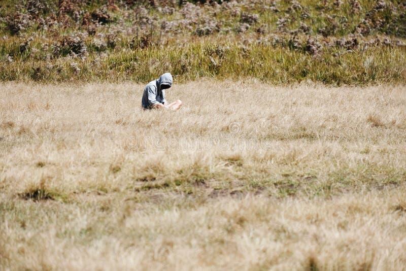 Solo hombre en la sudadera con capucha que se sienta solamente en el campo de hierba, individuo solo misterioso fotos de archivo libres de regalías