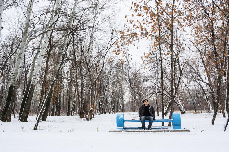 Solo hombre que se sienta en un banco en parque del invierno imagen de archivo libre de regalías