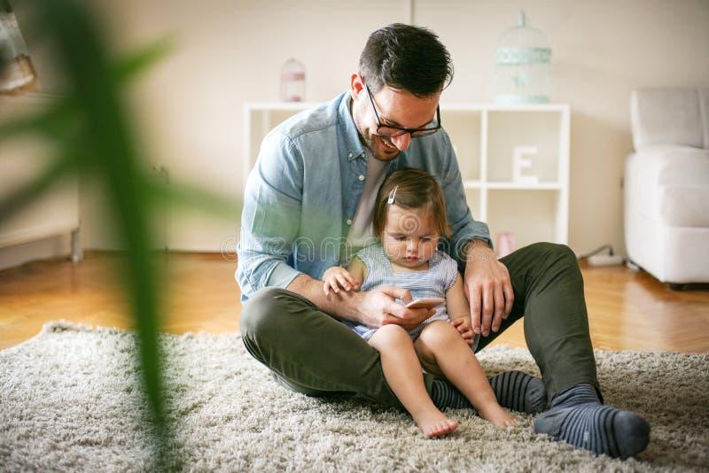 Solo ingenio del padre su hija que usa el teléfono elegante imagen de archivo