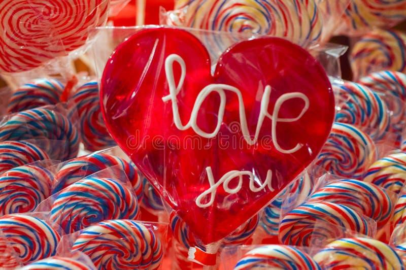 Solo lollypop rojo del caramelo con el texto blanco te quiero un polo con la trayectoria de recortes Parada con colorido y festiv fotografía de archivo libre de regalías