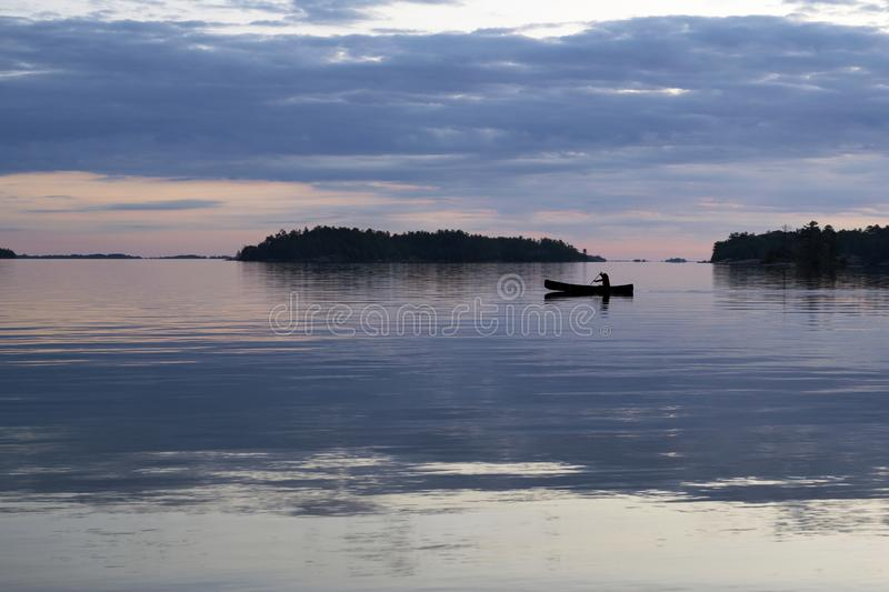 Solo paddling a canoe at dusk in Thirty-Thousand Islands, Ontario. A solo paddler in a canoe on a calm night in the Thirty Thousand Islands of Georgian Bay near stock photo