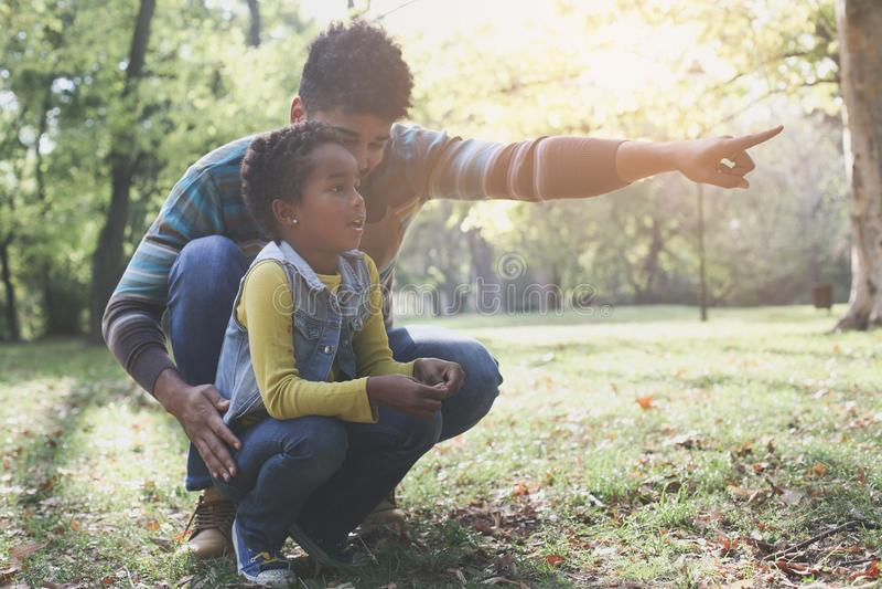 Solo padre afroamericano que muestra algo a su hija imagen de archivo