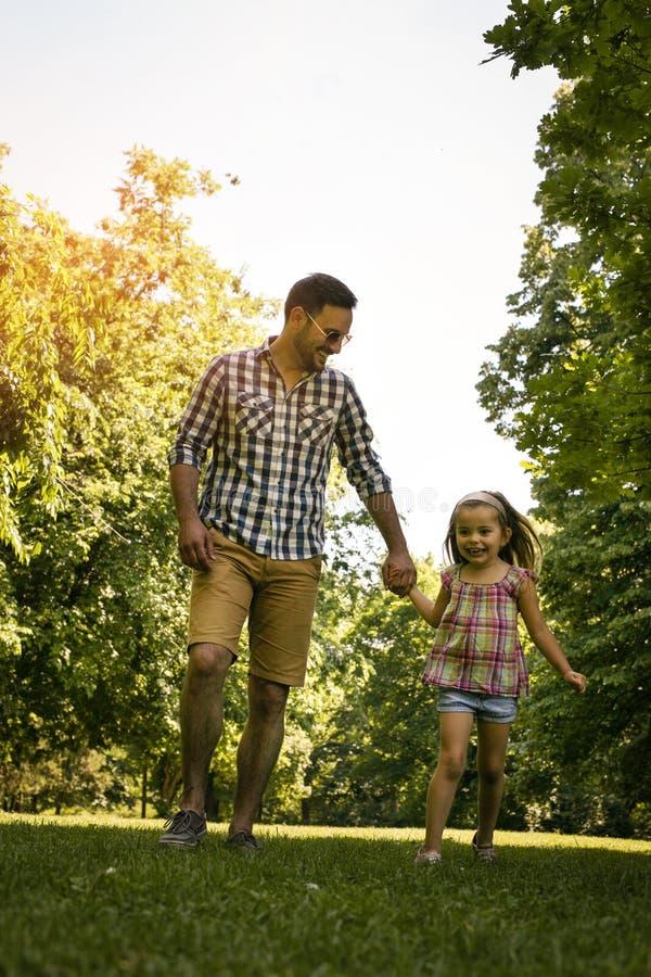 Solo padre que corre en el prado con la hija fotos de archivo
