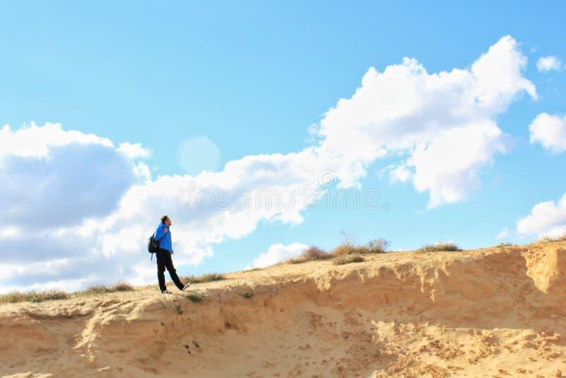 Solo reisender Mann mit Rucksack auf der Sanddüne mit Himmel und Wolkenhintergrund lizenzfreies stockbild