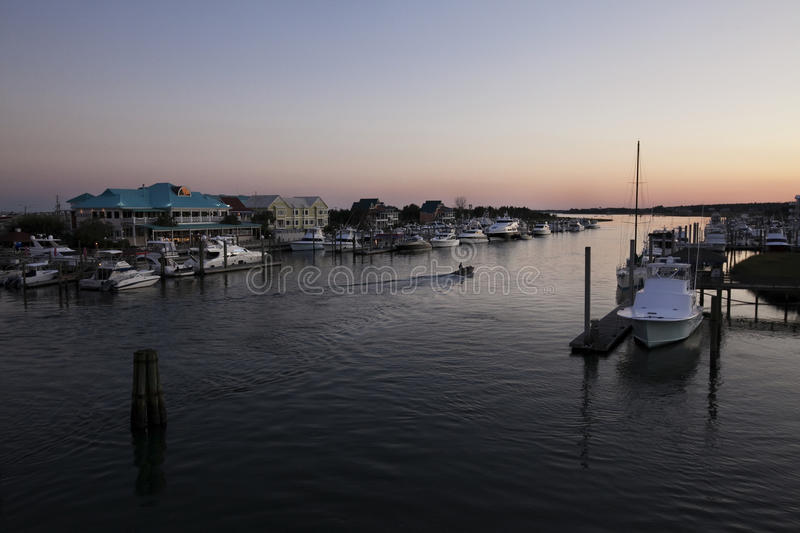Solo Sunset Boat Cruise by Bluewater. Pastel sunset with solo boat cruising through the inlet waterway. Bluewater Grill in background with blue roof. Image taken stock images