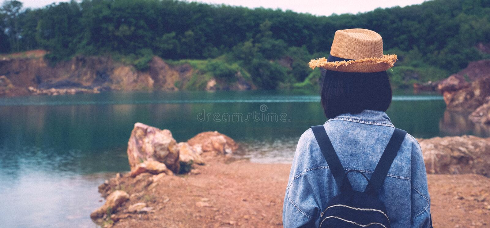 Solo travel in local asia, Back of teenager traveler walking on rock ground at lake lagoon, Woman tourist traveler standing at stock photos
