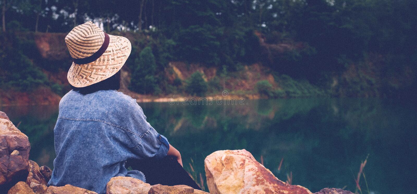 Solo travel in local asia, Back of traveler sitting on rock ground by lake lagoon, Woman tourist traveler sitting by local pond royalty free stock photo