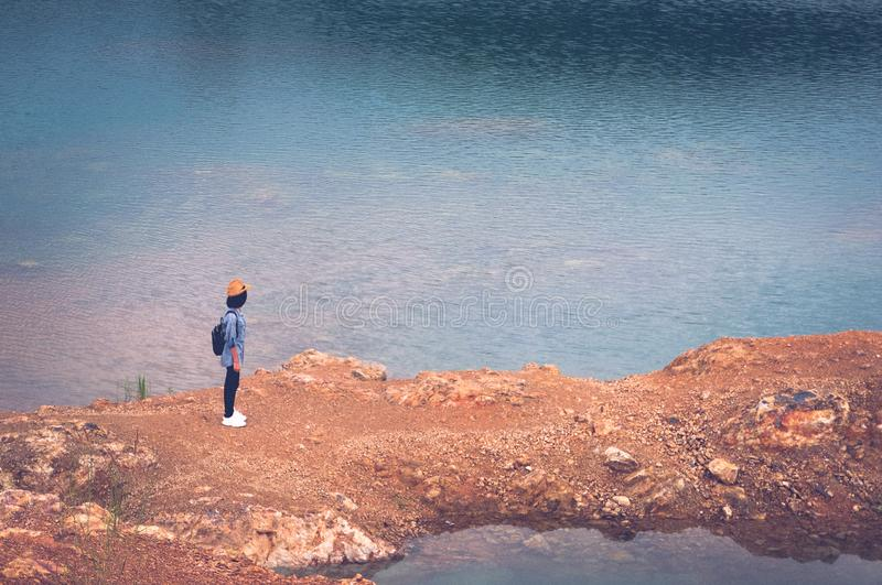 Solo travel in local asia, Teenager traveler walking on rock ground at lake lagoon, Woman tourist traveler standing and seeing stock images