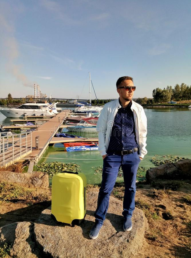 Dnipro, Ukraine - September 9, 2018: Solo traveling man with yellow luggage with yachts background stock image