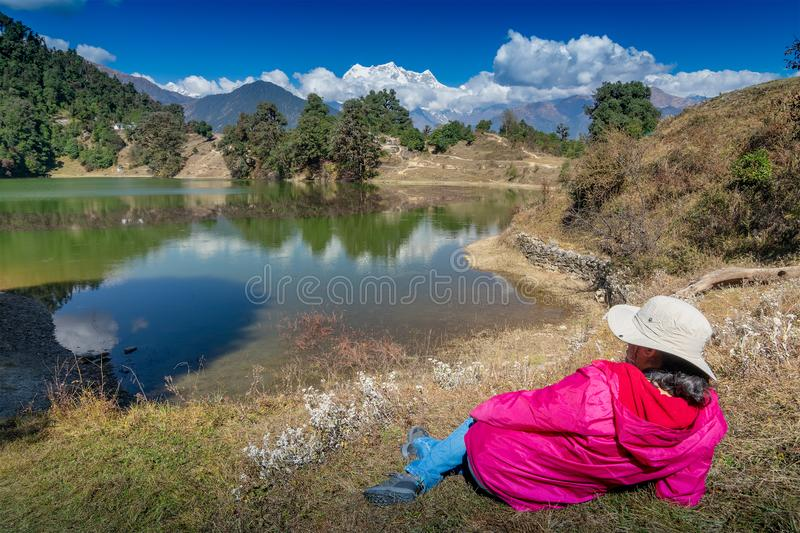 Deoria tal, uttarakhand, India. Solo traveller, single female tourist enjoying beauty of Deoria Tal while lying on green grass, high altitude lake in Uttarakhand stock photos