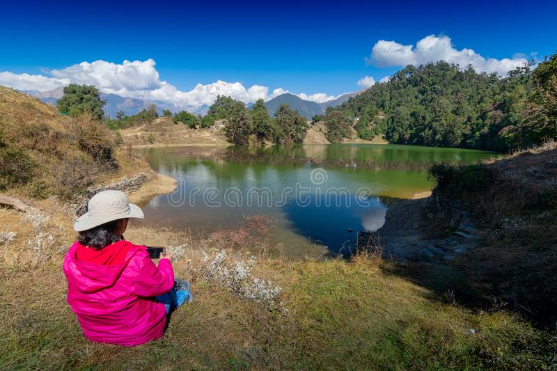 Deoria tal, uttarakhand, India. Solo traveller, single female tourist taking picture of Deoria Tal with her mobile phone, high altitude lake in Uttarakhand stock photography