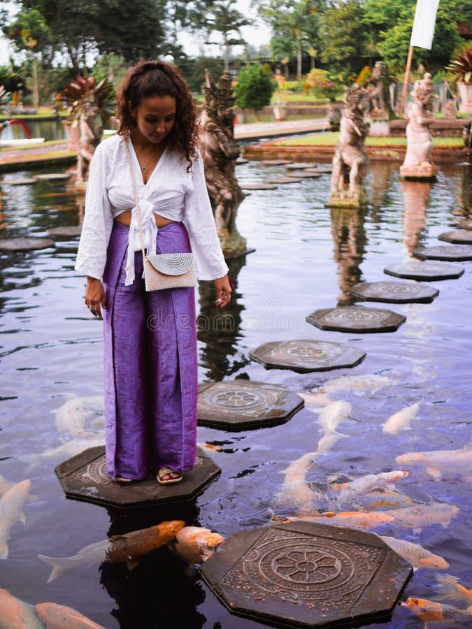 Solo Vrouwelijke Reiziger die Koi Fish op Springplanken voeden rond Koi Fish bij Hoofdfontein in Tirta Gangga, Bali royalty-vrije stock afbeeldingen