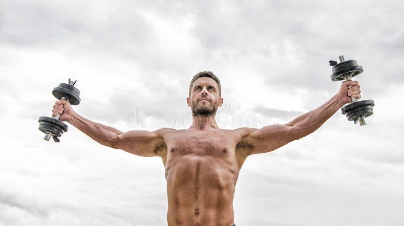 Solo vuelo. halterofilia de hombre libre. esteroides. cuerpo atlético. Gimnasio del Dumbbell. Hombre muscular haciendo ejercicio  fotografía de archivo