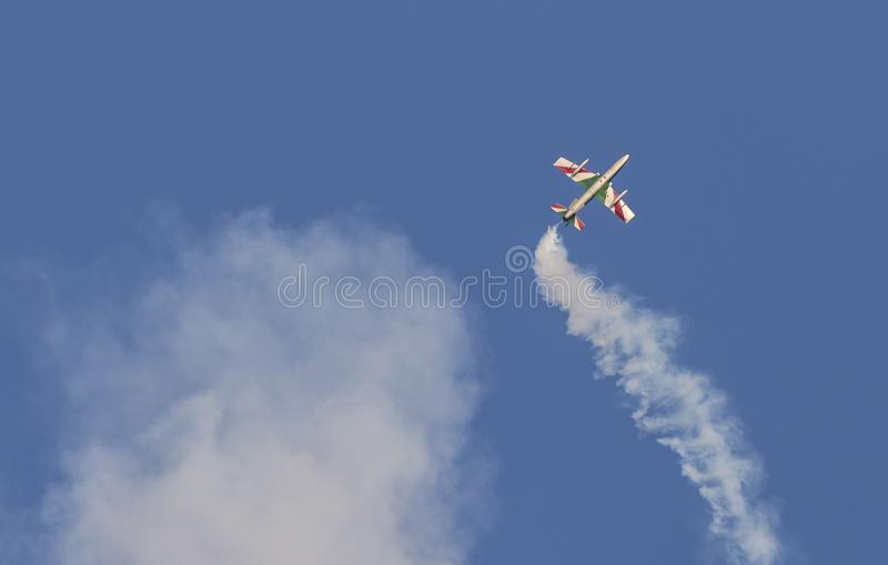 Plane jet of Soloist at the italian tricolor arrows air show performs the acrobatic figure `dead leaf` royalty free illustration