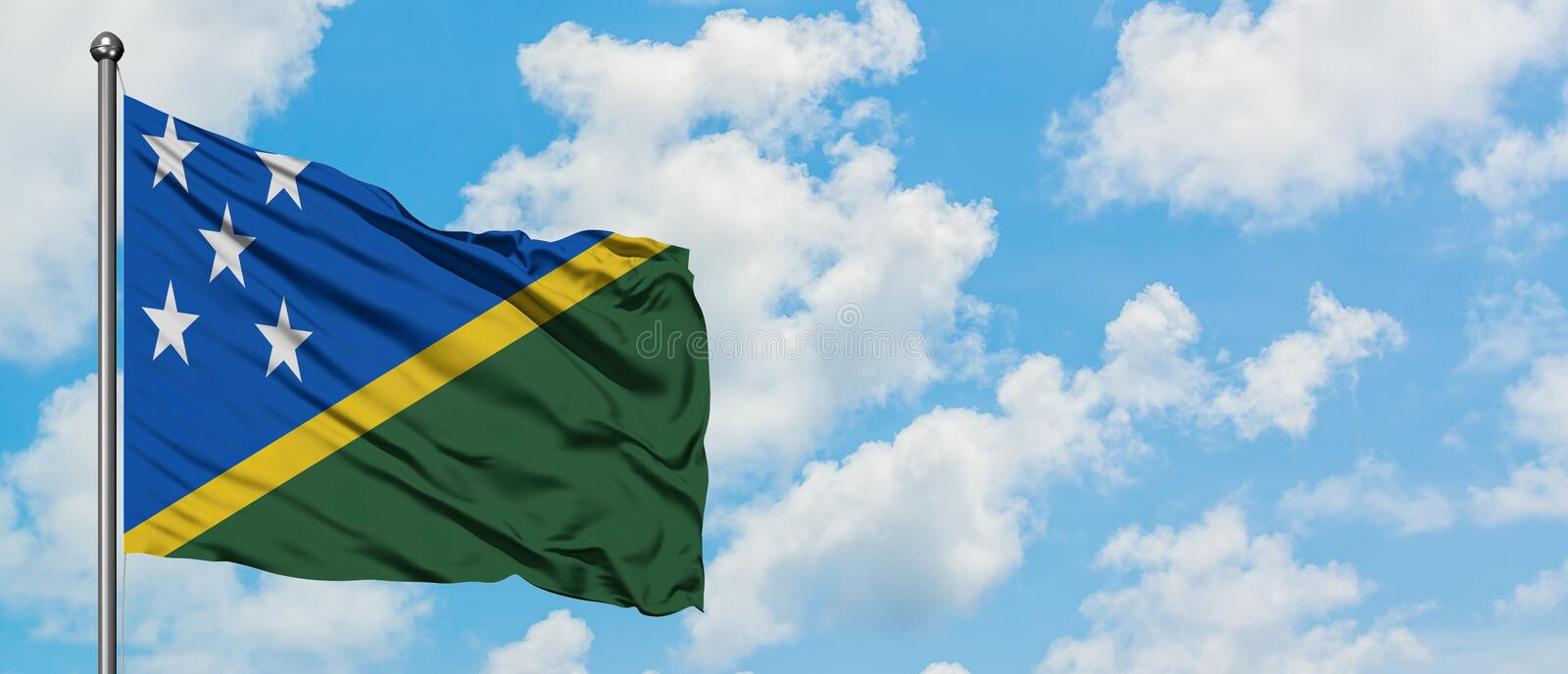 Solomon Islands flag waving in the wind against white cloudy blue sky. Diplomacy concept, international relations.  stock photo