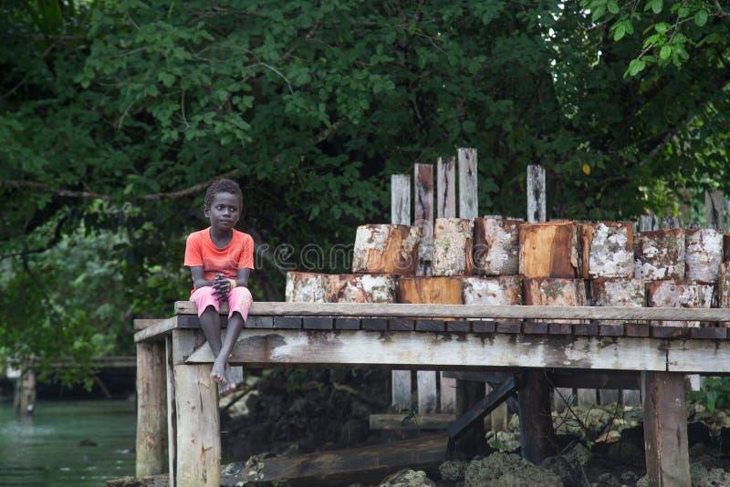 Solomon Islands, muchacho que se sienta en un embarcadero fotografía de archivo libre de regalías