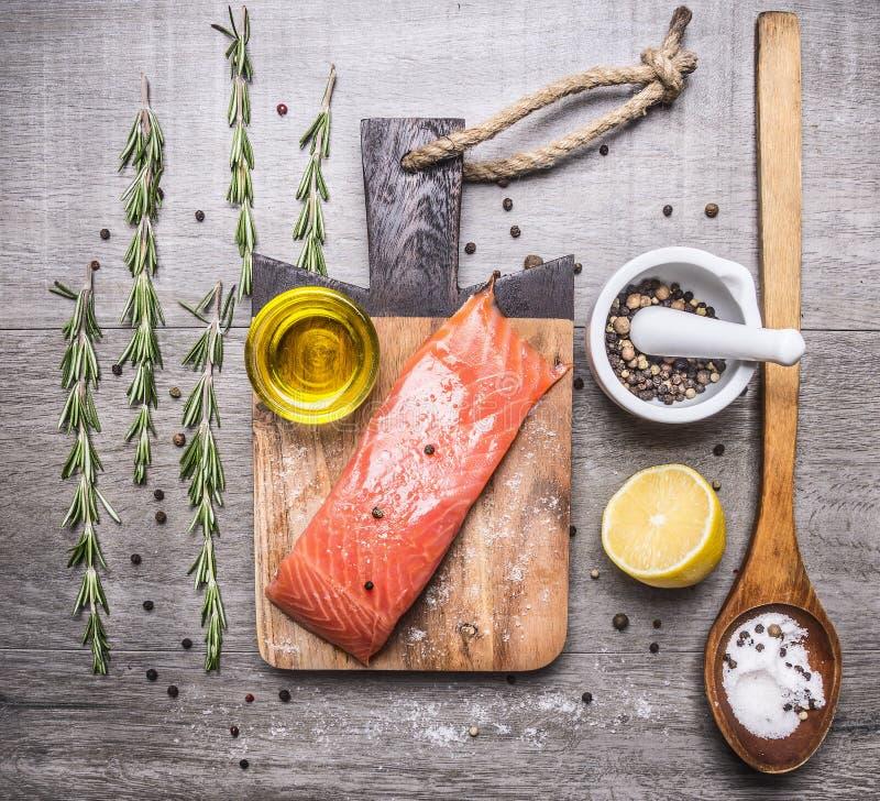 Solony łosoś polędwicowy na tnącej desce z rozmarynami, pieprzem, olejem, cytryną i drewnianą łyżki solą na drewnianym nieociosan zdjęcia stock