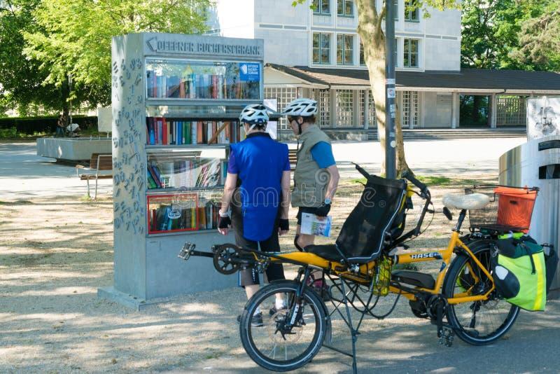 Solothurn, ASSIM/Suíça - 2 de junho de 2019: turistas do biccle para parar e apreciar os livros em uma das bibliotecas abertas li imagem de stock